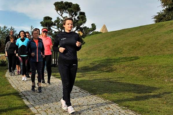 Edyta Dawiskiba truchtajaca slow jogging z grupa w plenerze